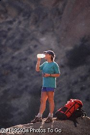 Woman drinking during mountain climb